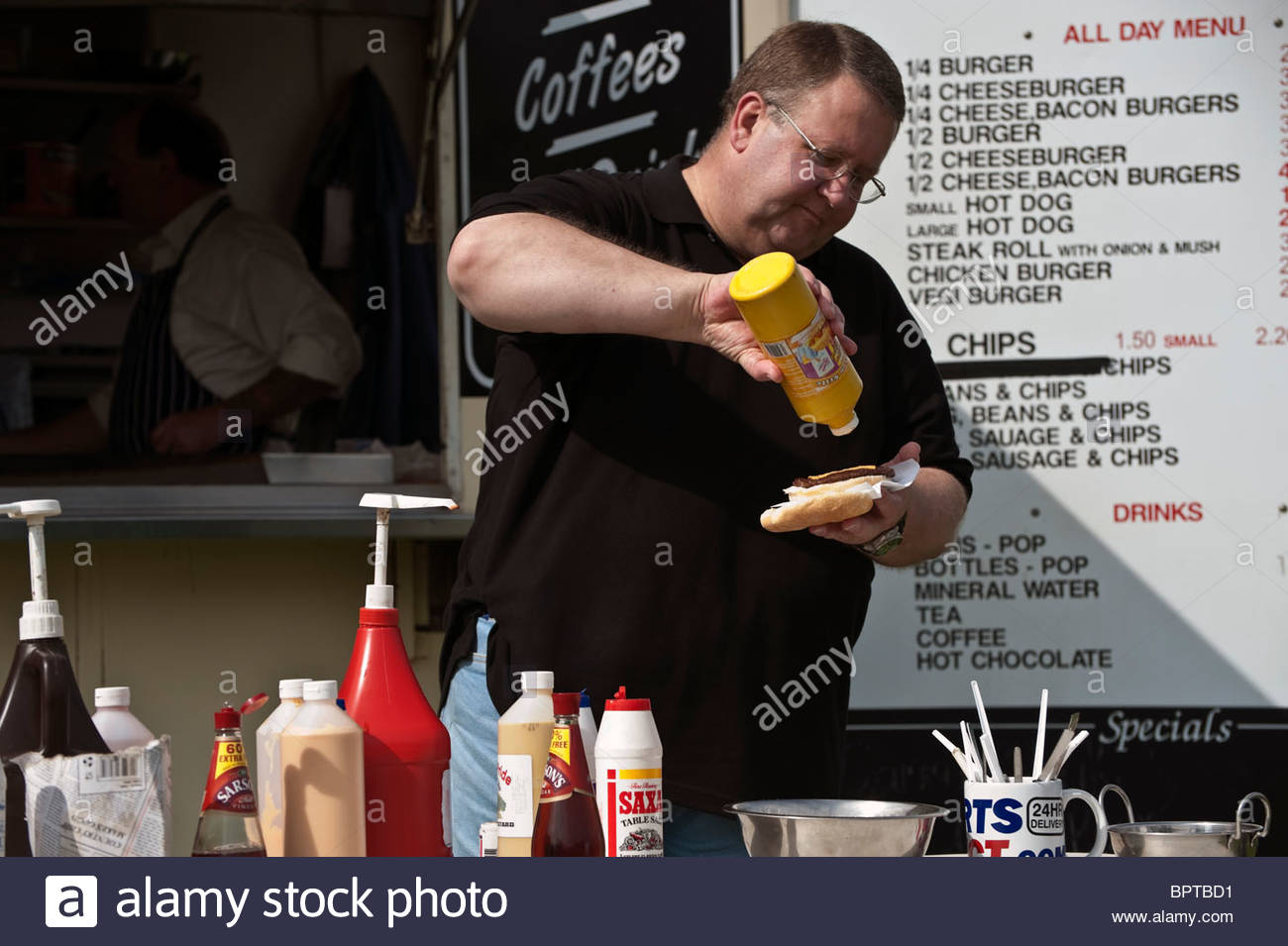 Fat man eating junk food at an outdoor catering van, UK. Overweight man eating a burger, outside. - Stock Image