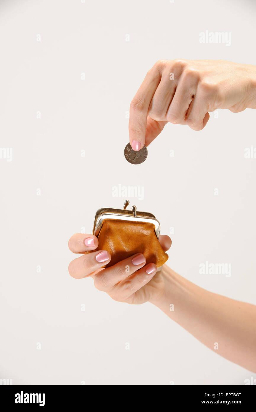 woman puts quarter into coin purse - Stock Image