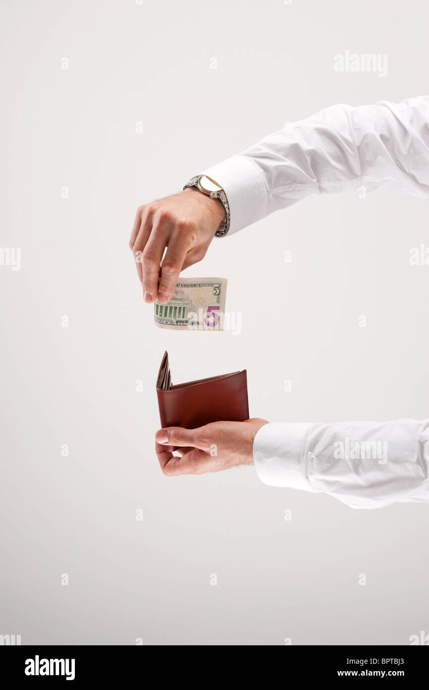 Man puts five dollars into wallet - Stock Image