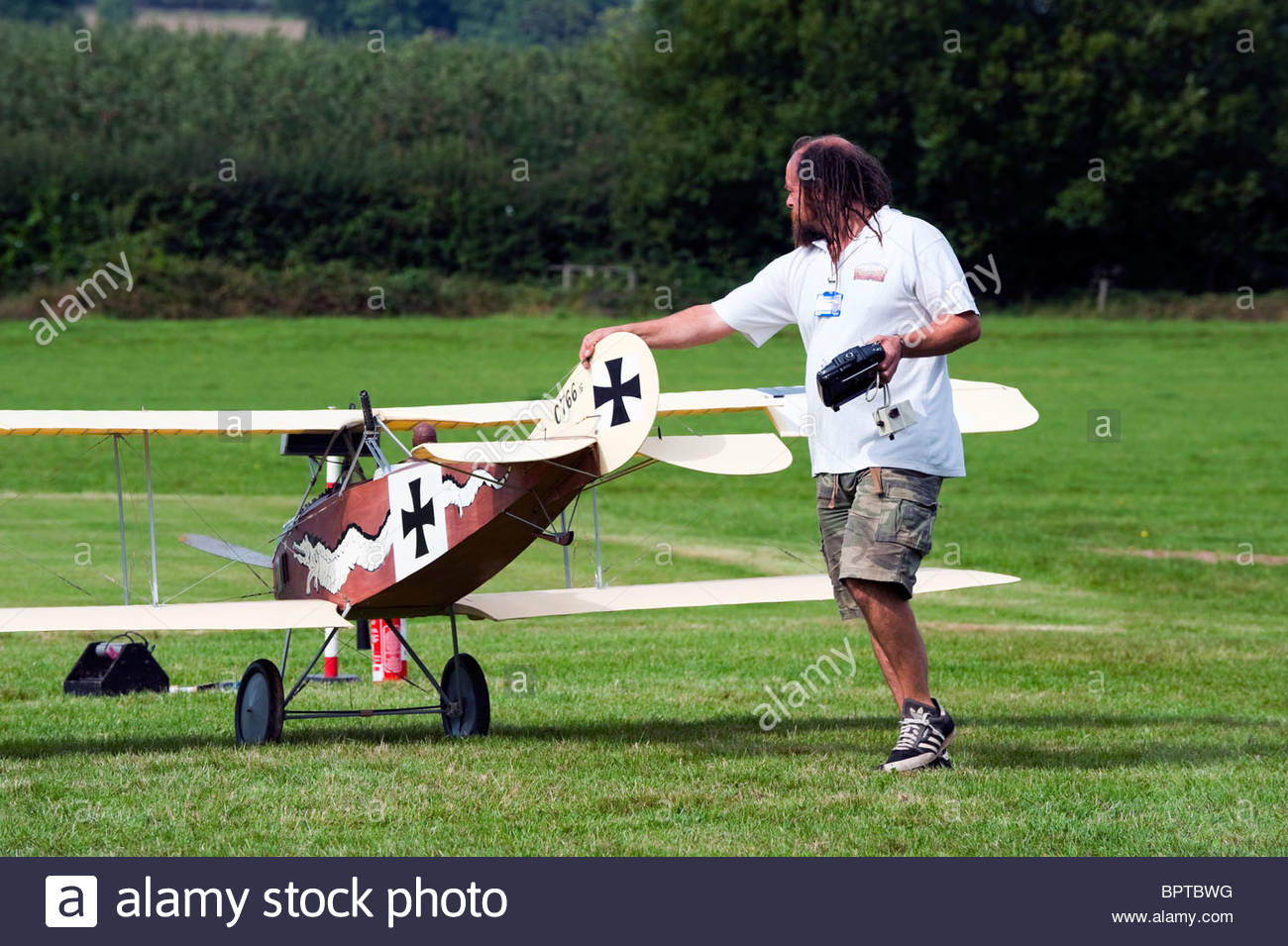 Large model aircraft flying display at Much Marcle, Herefordshire, UK. Man with large radio controlled biplane. - Stock Image