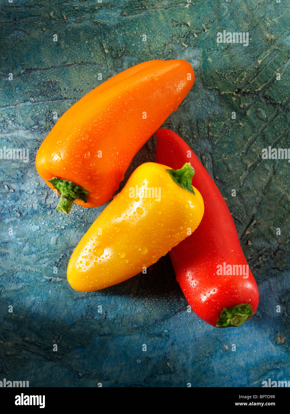Mixed red, yellow & orange fresh mini peppers photos, pictures & images - Stock Image