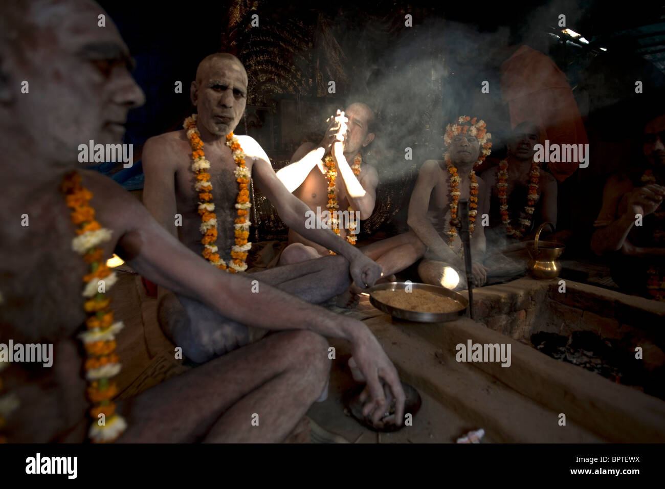 Holy Sadhus men smoking hash at early morning in preparation for the Kumbh Mela festival Haridwar, Uttarakhand, - Stock Image