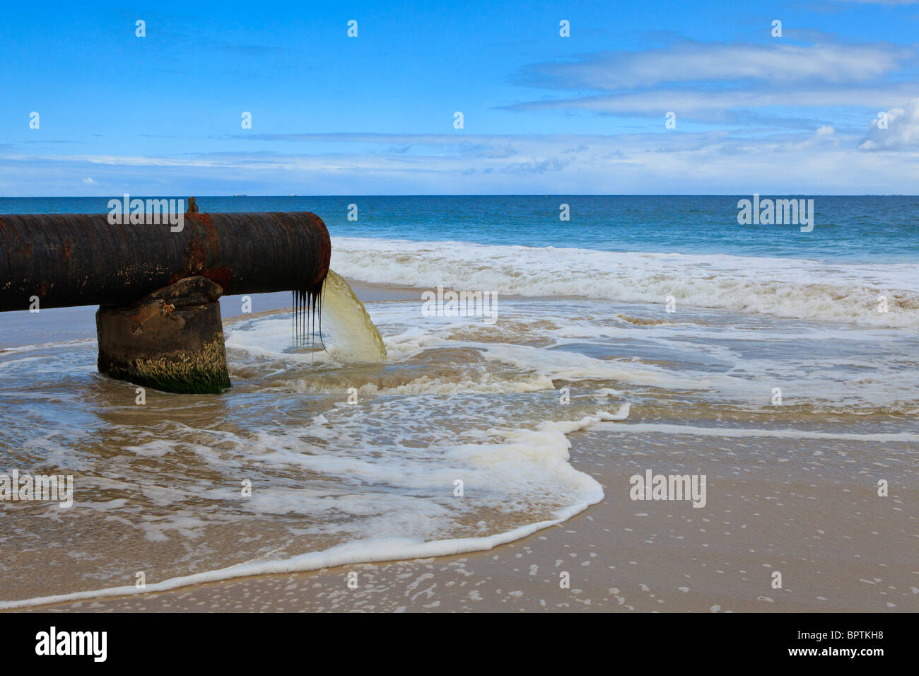 Rainwater drain pipe pouring out onto a beach. - Stock Image