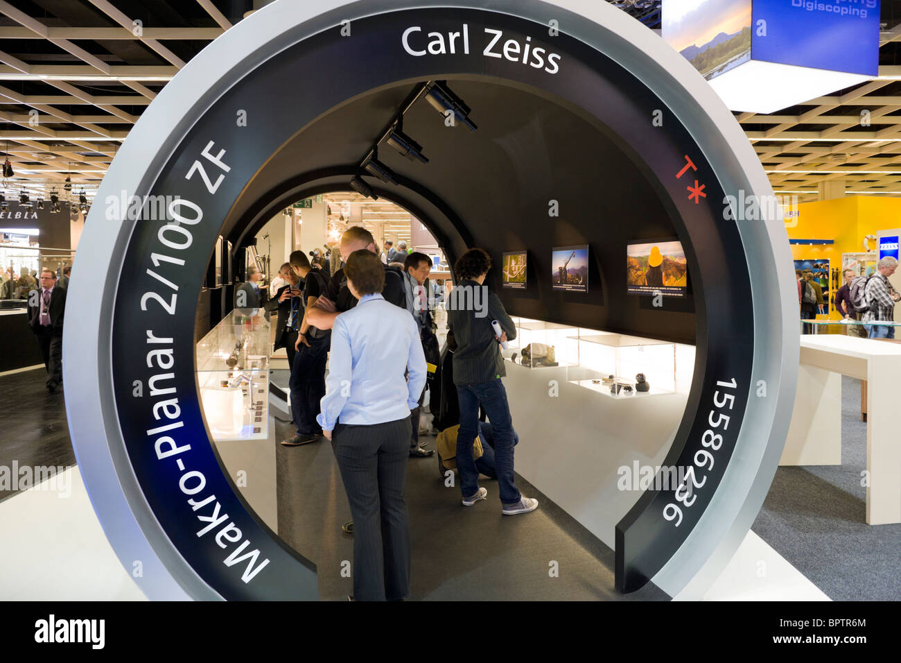 Visitors at the 2008 Photokina camera trade show in Cologne Koeln Germany. Carl Zeiss booth in the form of a Macro - Stock Image
