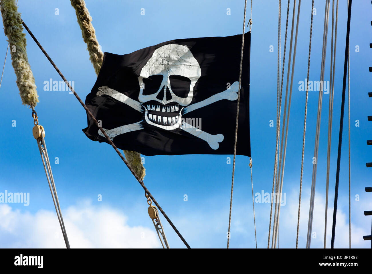 Skull and crossbones, Jolly Roger, a pirates' flag flying on a historic tall ship - Stock Image