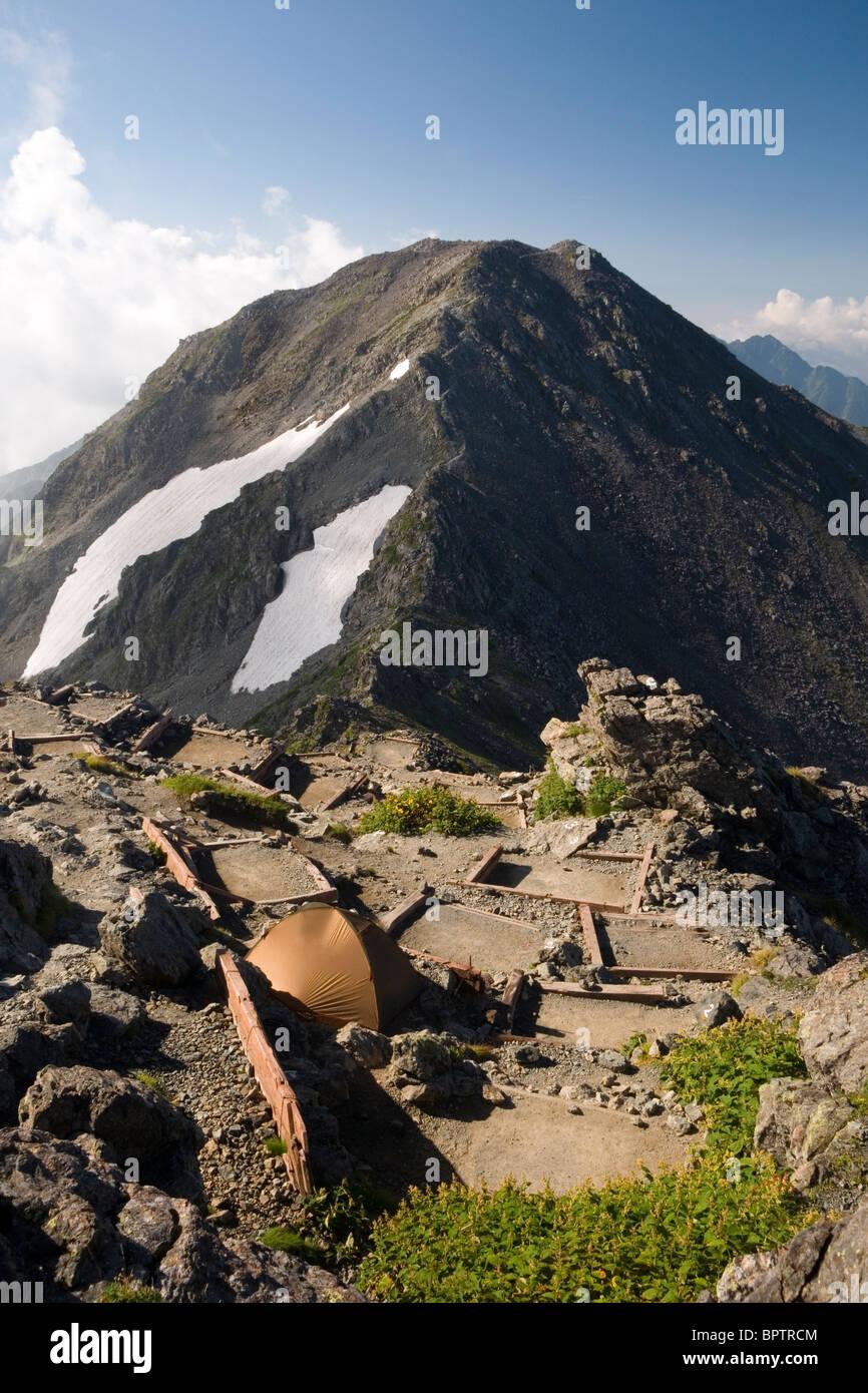 A tent at the Yari-ga-take campsite with a view of Naka-dake. Kita Alps, Nagano, Japan - Stock Image