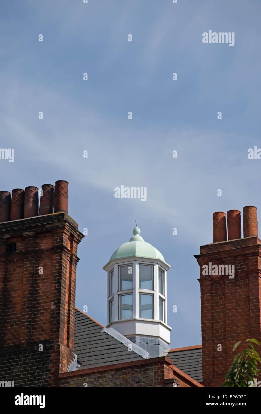 windowed cupola between tudor style redbrick chimneys on a  rooftop in cheyne walk, chelsea, london, england - Stock Image