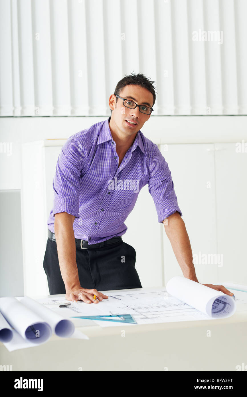 portrait of mid adult architect leaning on desk and looking at camera - Stock Image