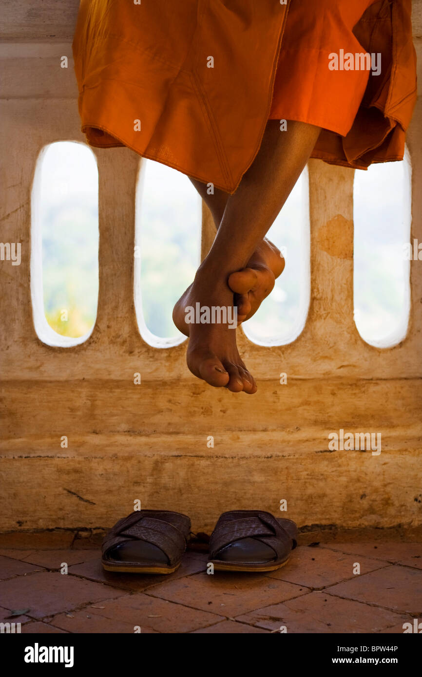 Detail of a monk sitting on a wall at Mount Phu Si in the centre of old town Luang Prabang, Laos. Indochina. Southeast - Stock Image