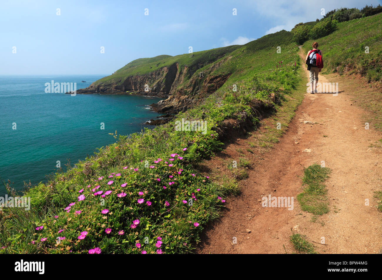 A woman hiking along the beautiful coastal path of North Herm in the Channel Islands of England - Stock Image