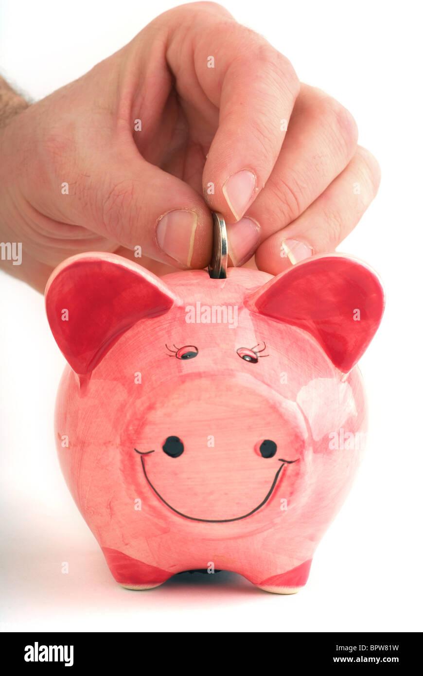 Filling up piggy bank studio isolated on white background - Stock Image