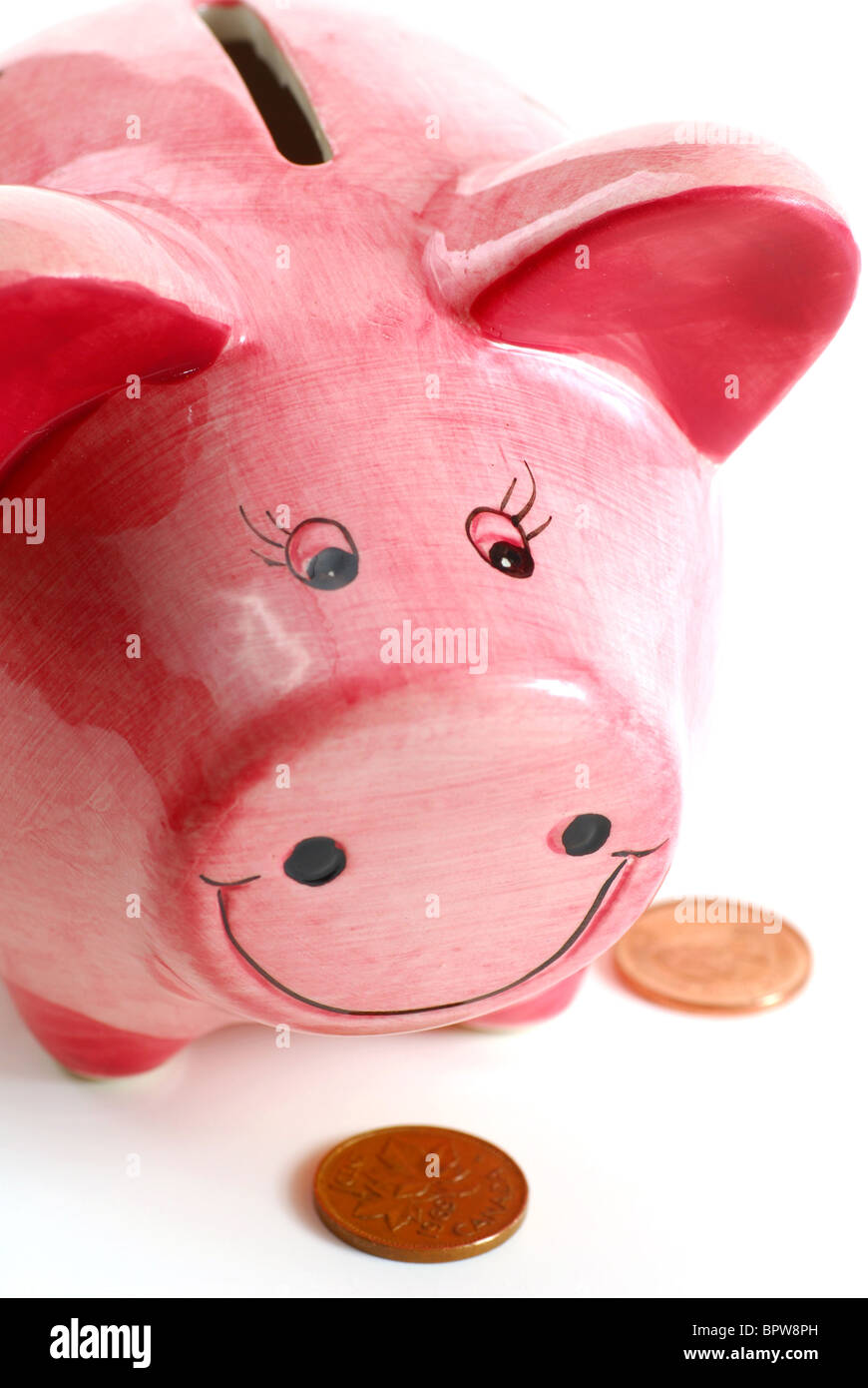 Pink piggy bank with coins on white background - Stock Image