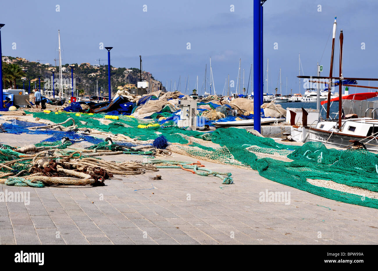 View of the the fishing harbor (port) along the quayside in Puerto Andtatx with colorful fishnet and an anchor - Stock Image