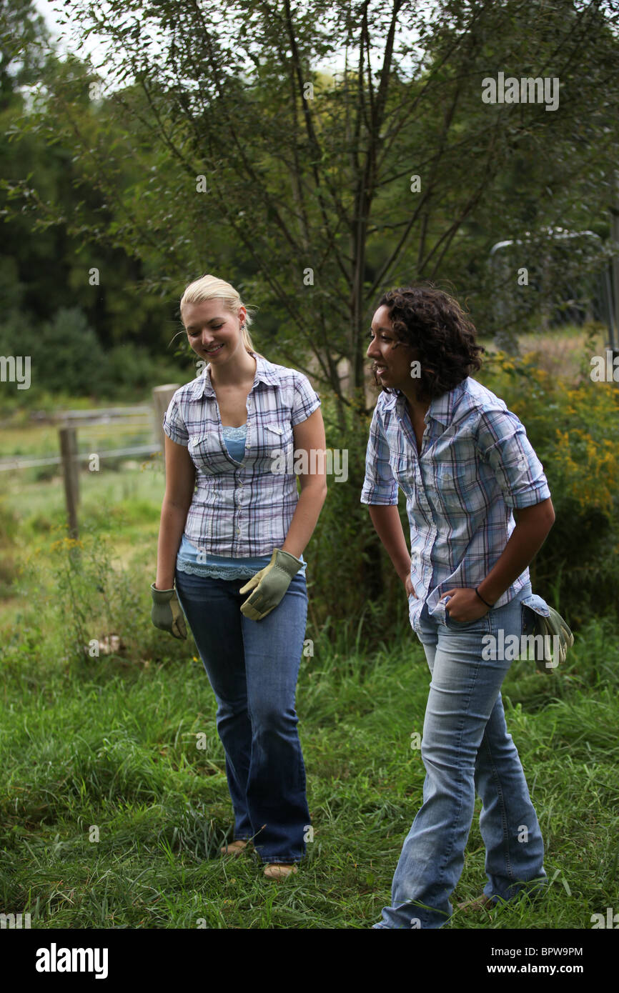 Two young ethnic diverse women doing chores and farm work together - Stock Image