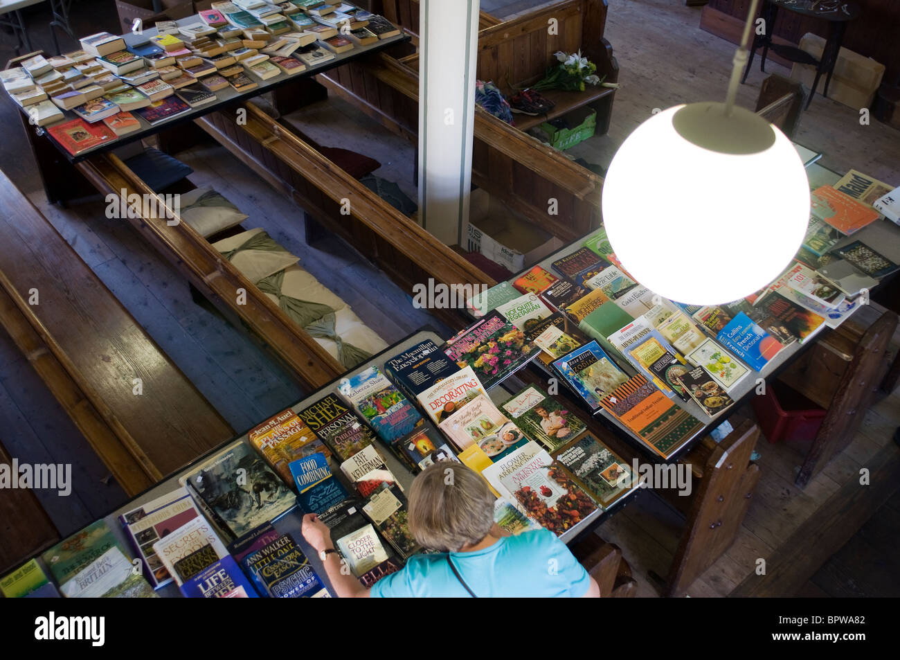 Jumble of second hand books for sale on chapel pews England,Chapel pews from above - Stock Image