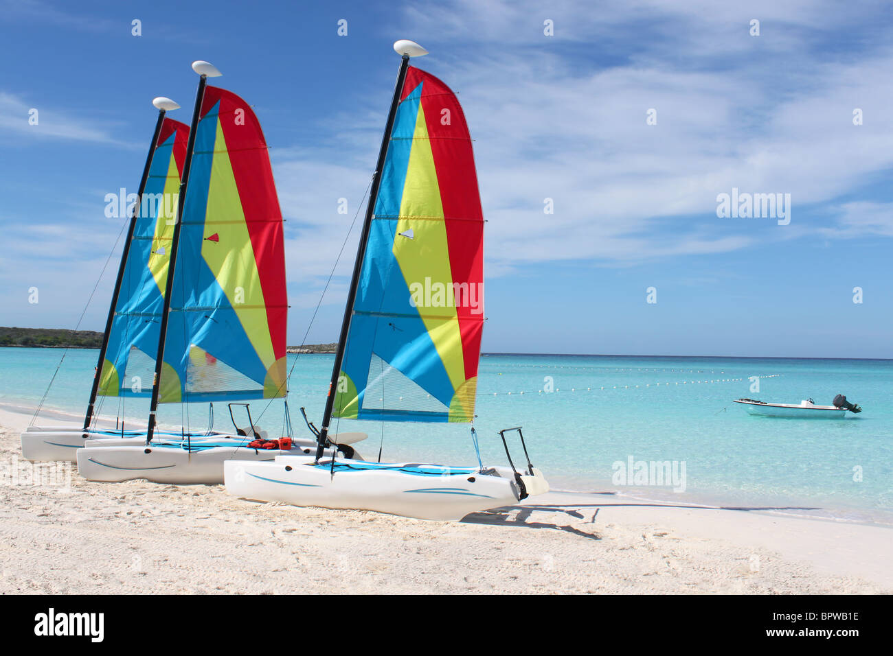 Colorful sailboats for rent on a tropical beach at Half Moon Cay in the Bahamas - Stock Image