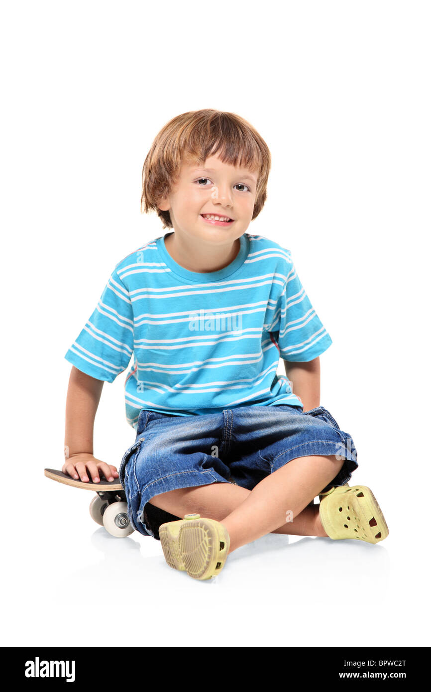 Adorable young boy sitting on a skateboard - Stock Image