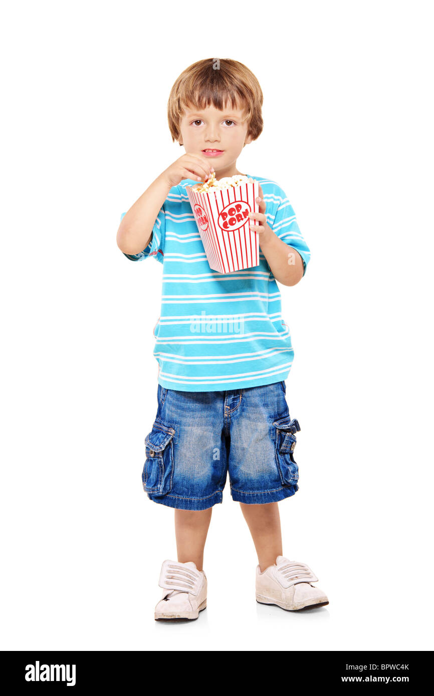 Full length portrait of adorable young boy eating popcorn - Stock Image