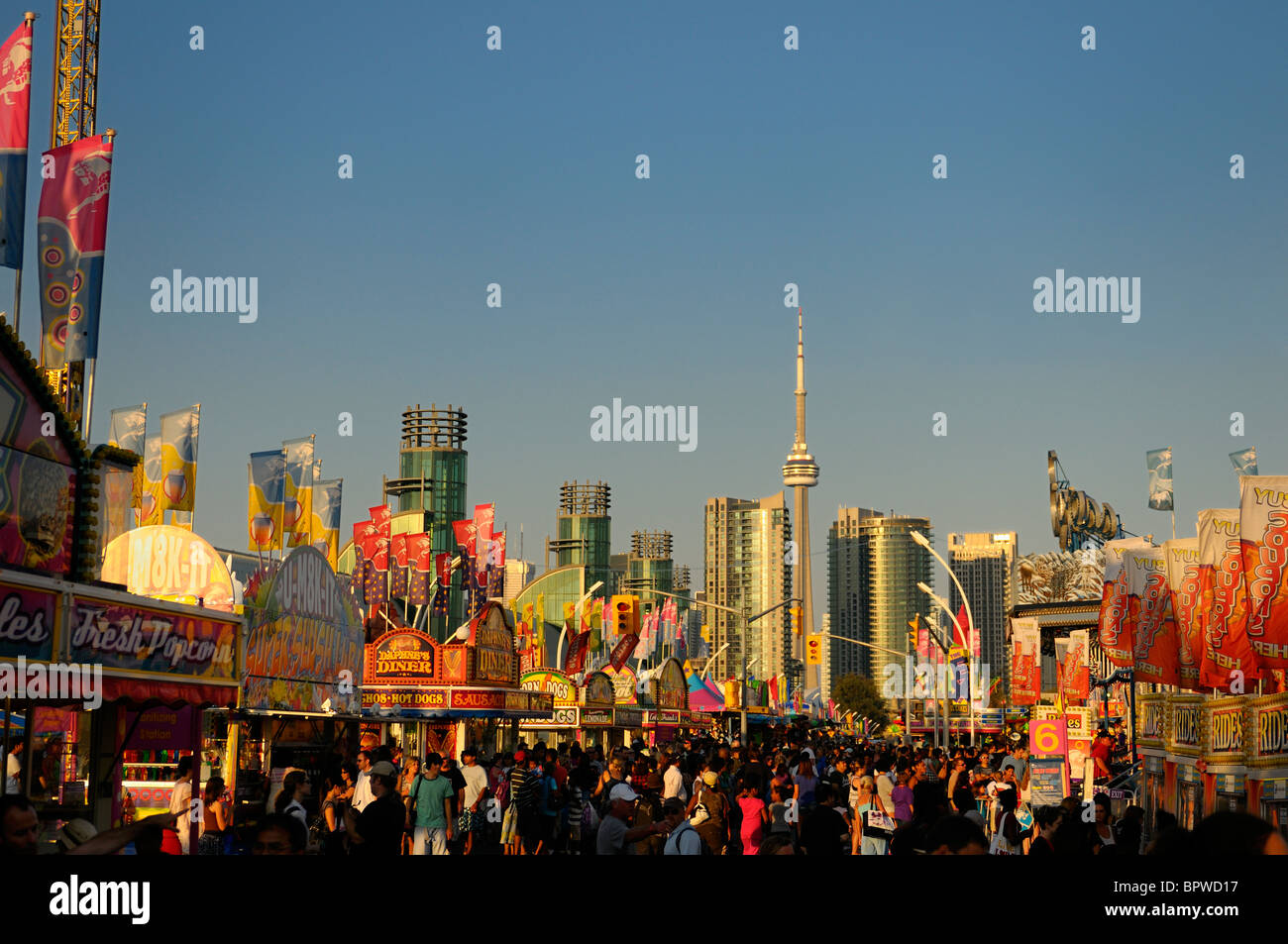 Canadian National Exhibition fair along the midway at sundown with Toronto skyline - Stock Image