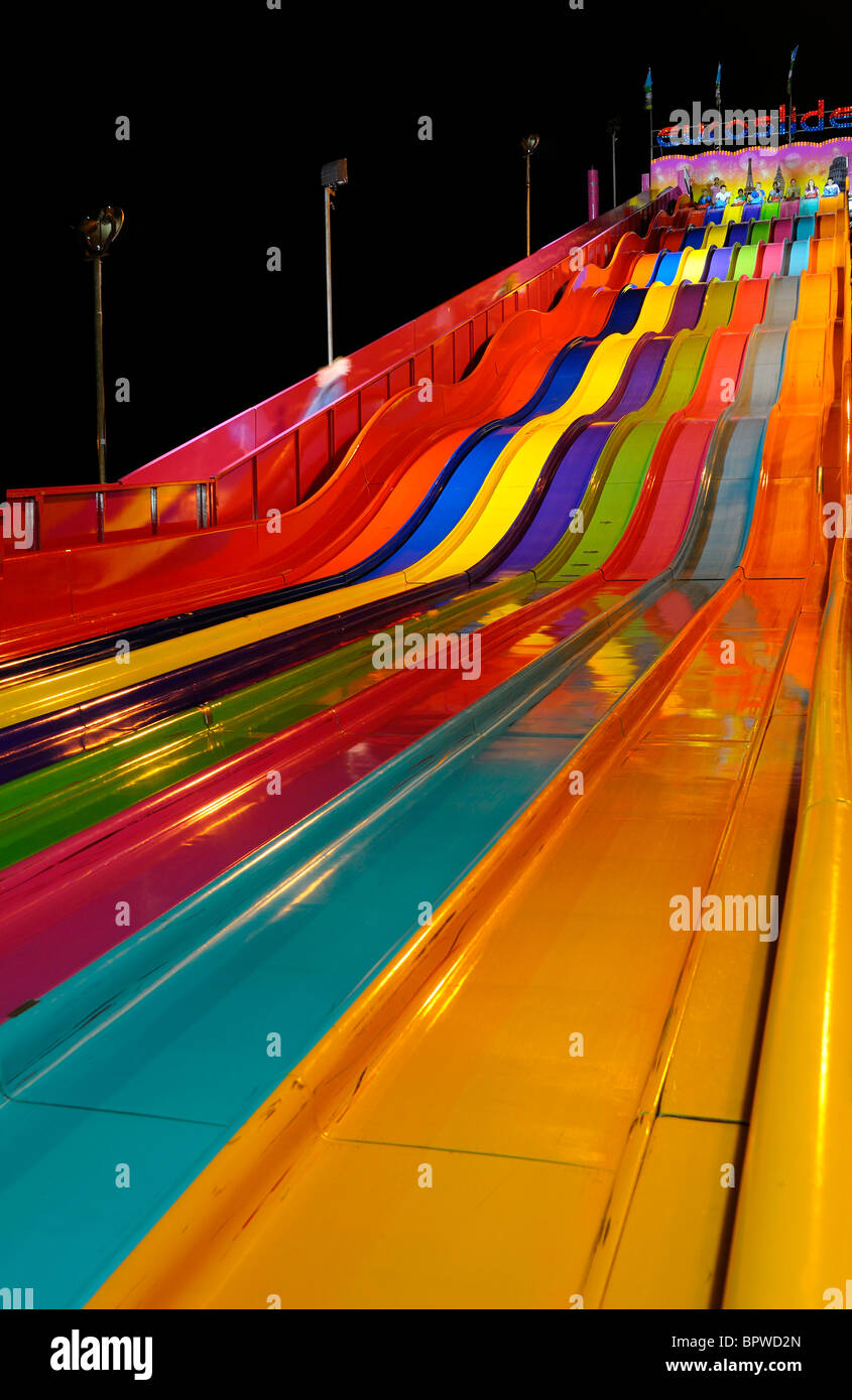 Waves of color at the funfair carpet slide at the CNE Toronto at night - Stock Image