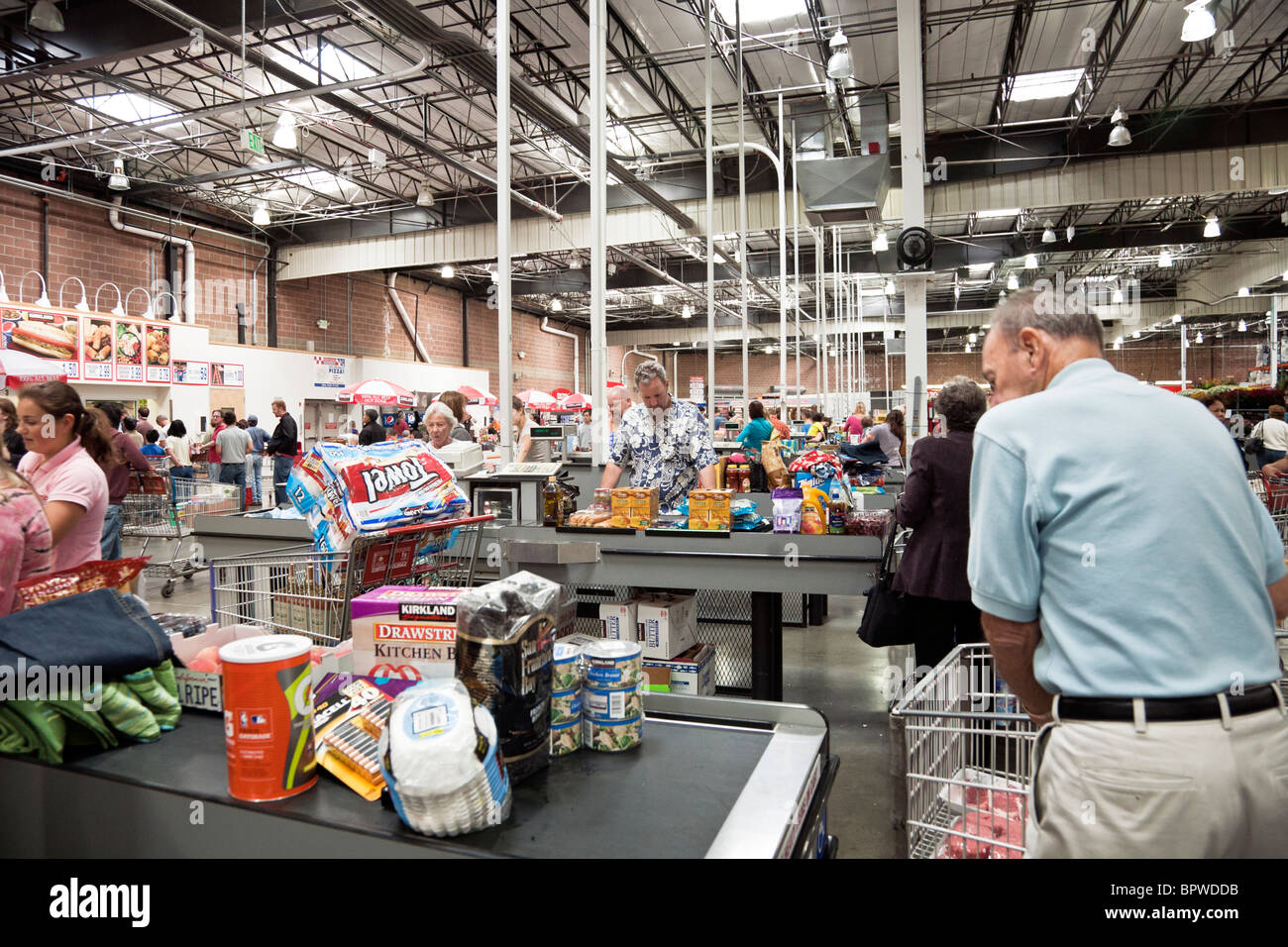 people pass through rows of checkout counters loaded with consumer purchases at a Costco USA  big box retailer - Stock Image