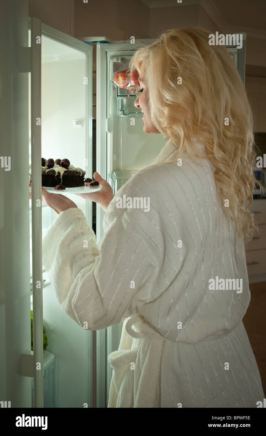 young woman getting a cake out of fridge midnight snack - Stock Image