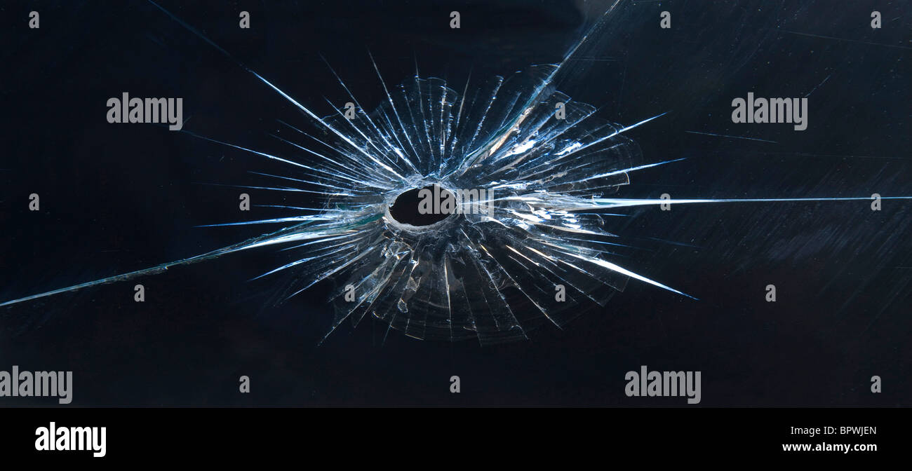 Bullet hole in the glass of the window of my studio. - Stock Image