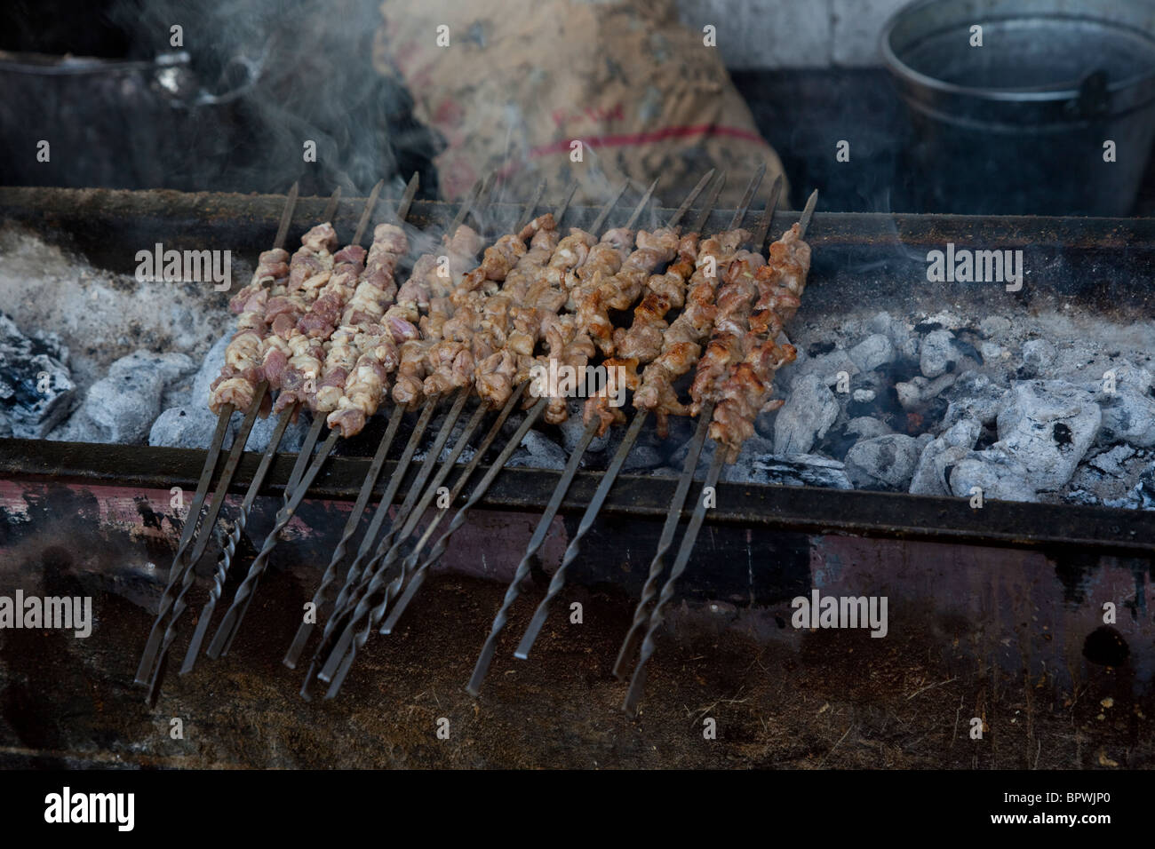 Meat being grilled at the bazaar in Turpan, Xinjiang, China. - Stock Image
