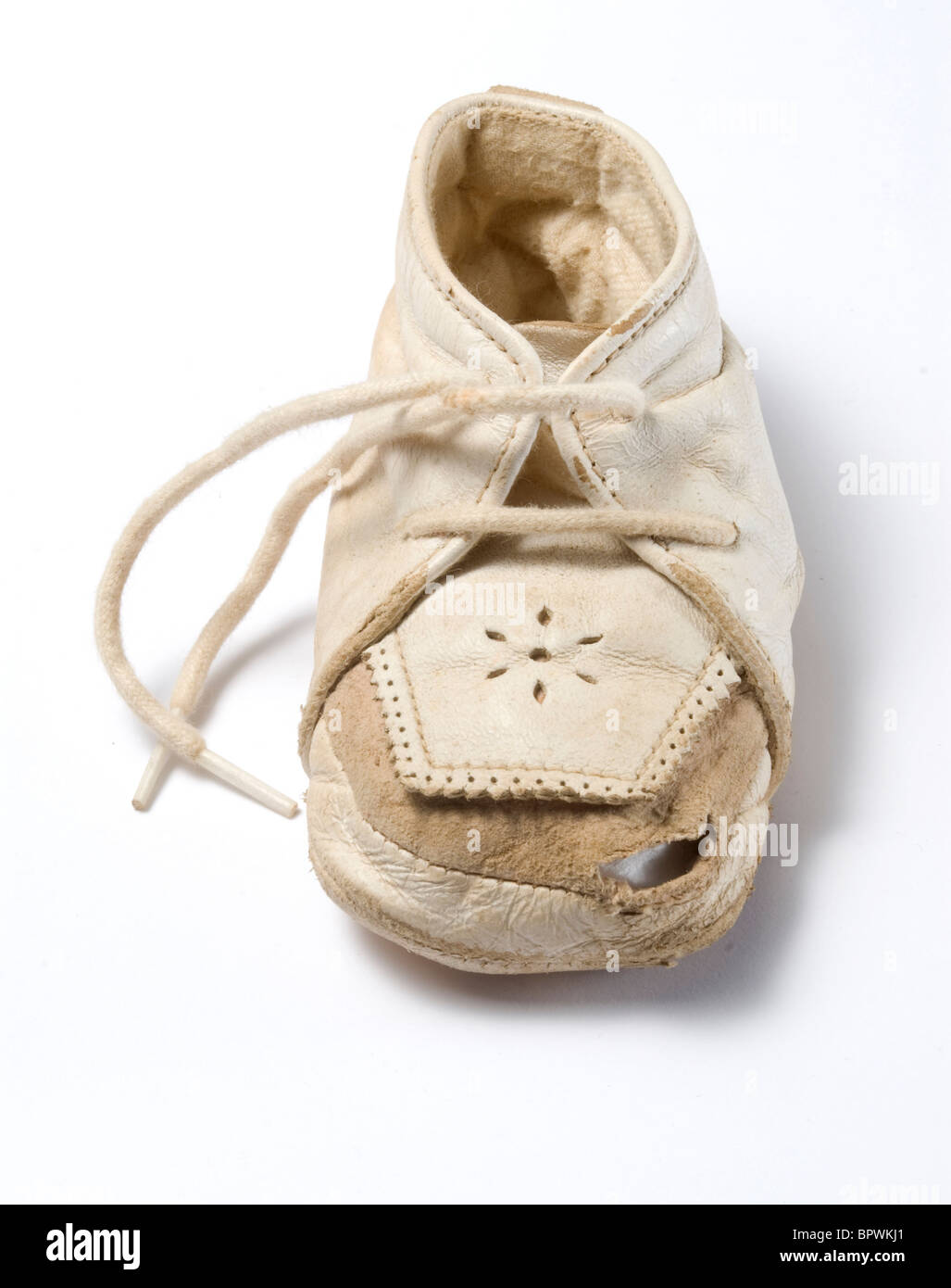 A baby's old white leather shoe with a hole in the toe - Stock Image