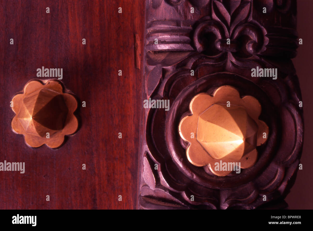 Detail of brass spikes and studs on a beatifully wooden carved door in Stone Tow Stock Photo
