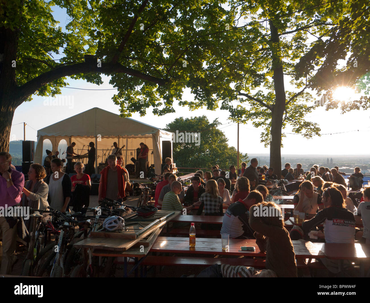 Sitting in the evening sun, visitors of the Freiburg Schlossberg festival in Southern Germany listen to a music - Stock Image