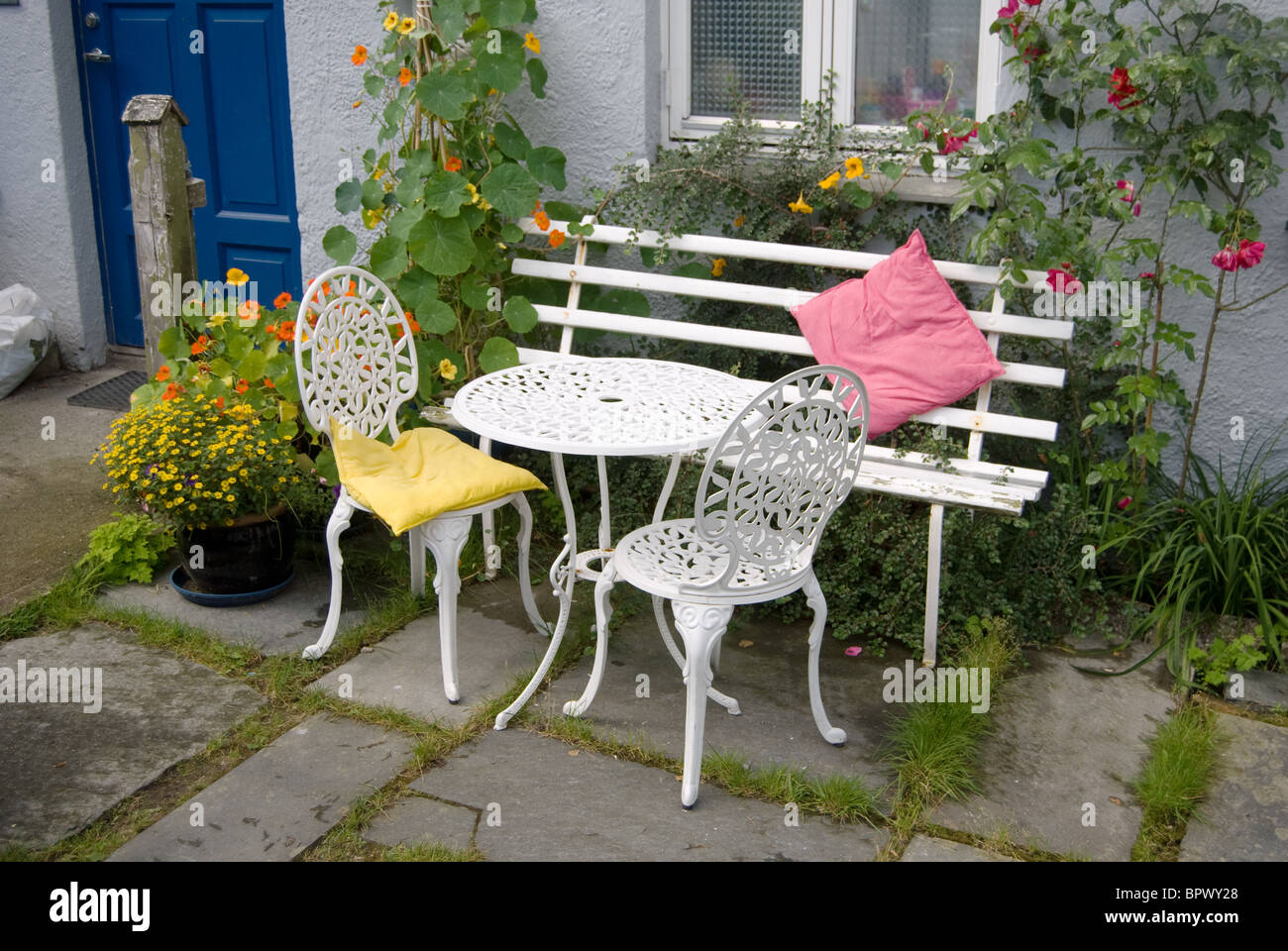 welcome scene, sweet home, white bench, table and two chairs in front yard of a house - Stock Image