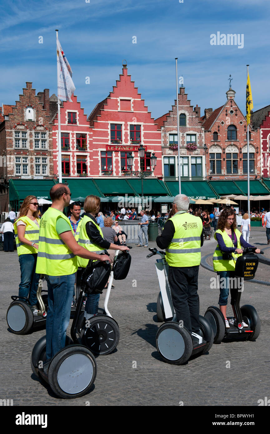 Group of tourists on tour of historic Bruges on Segway electric vehicles in Belgium - Stock Image