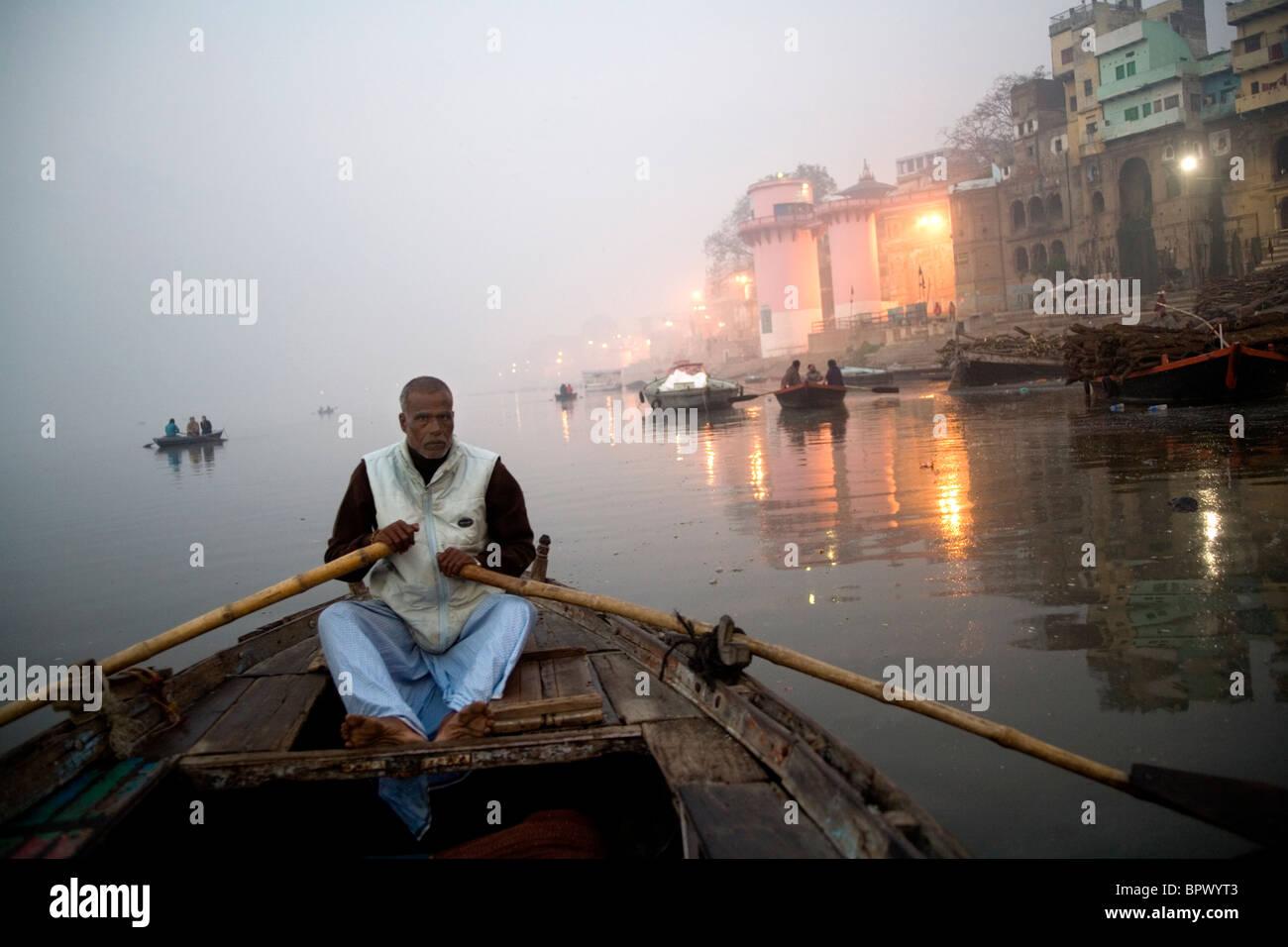 Man rowing a small boat on the River Ganges Varanasi at early morning, Uttar Pradesh, India. - Stock Image