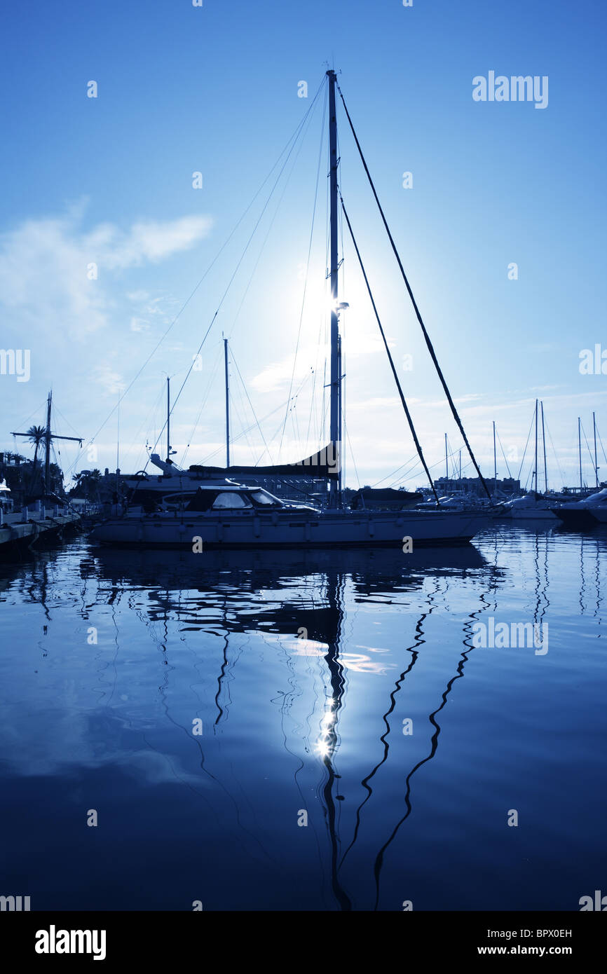 blue marina sunset boats with water reflection nautical view - Stock Image