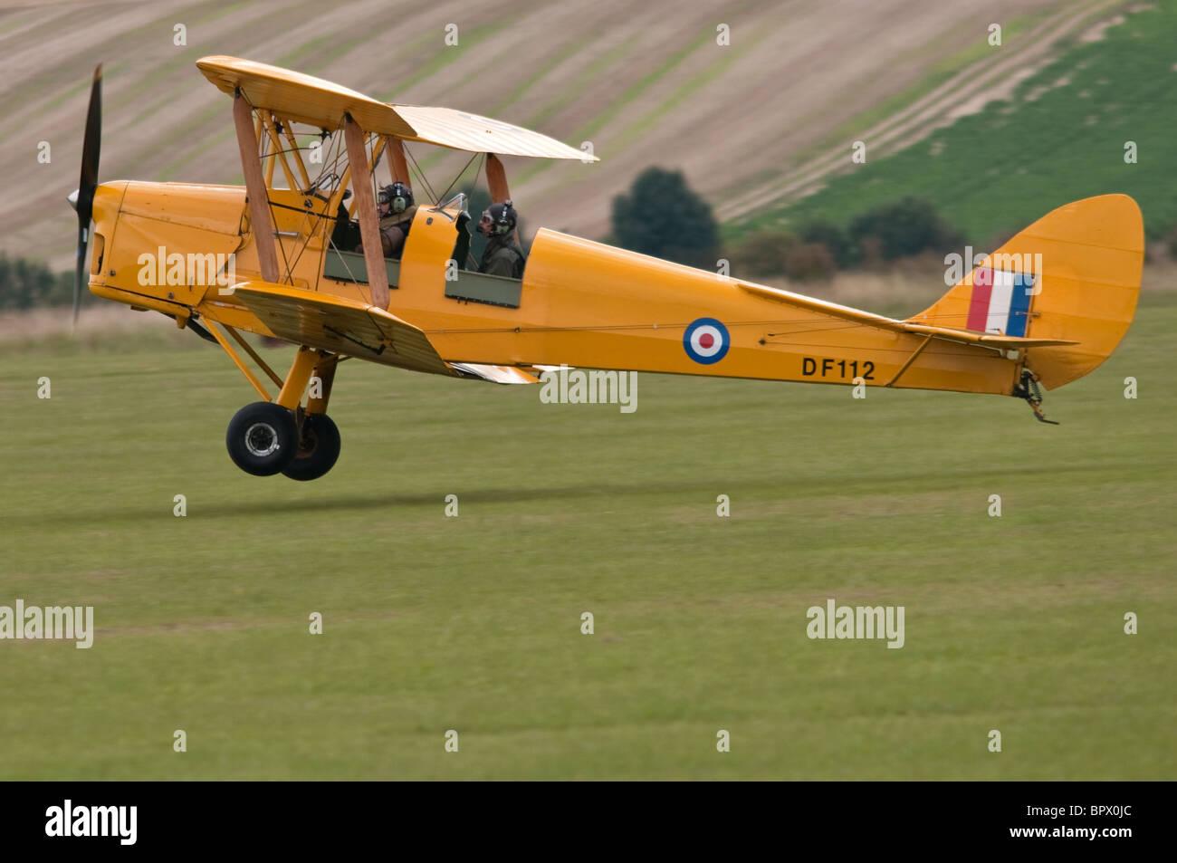 de Havilland DH 82 Tiger Moth landing at Duxford - Stock Image