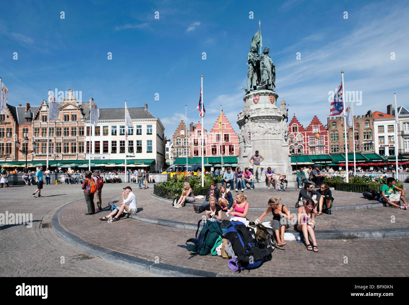Tourists sitting in the famous historic Market Square in Bruges in Belgium - Stock Image