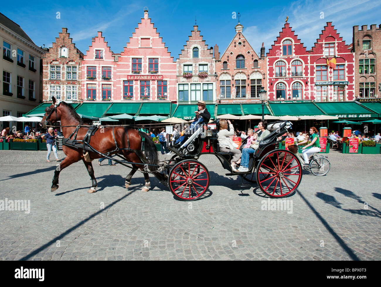 Tourists enjoying tour of Bruges in Belgium on horse drawn carriage - Stock Image