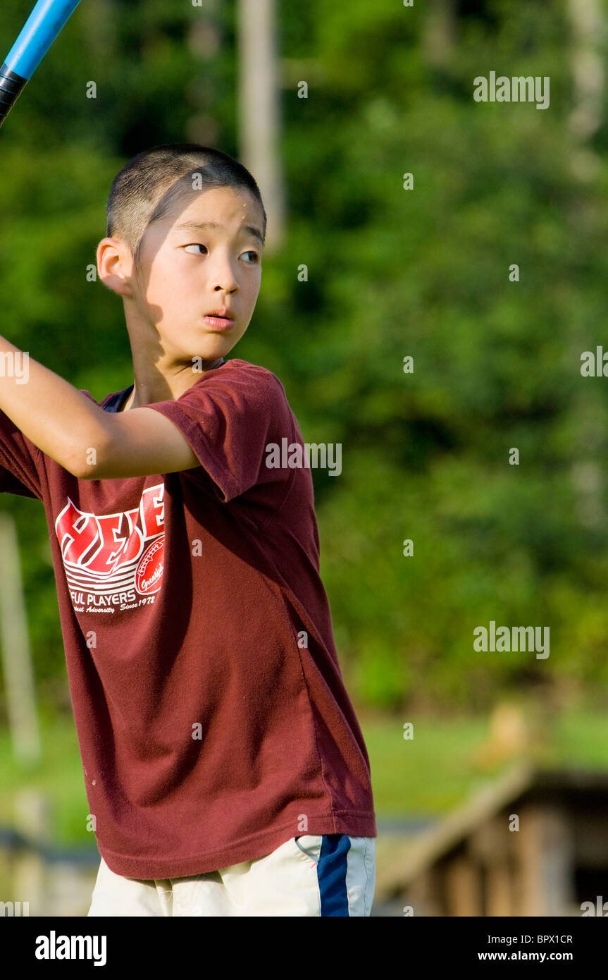Japanese boy prepares to swing a baseball bat in a park - Stock Image