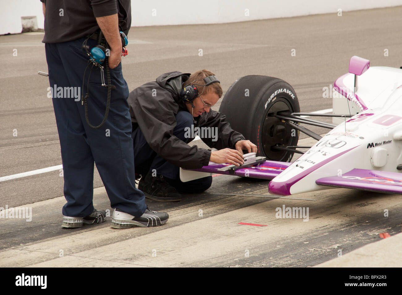 Pit crew member adjusts front wing of IndyCar during 2010 500 practice at Indianapolis Motor Speedway. - Stock Image