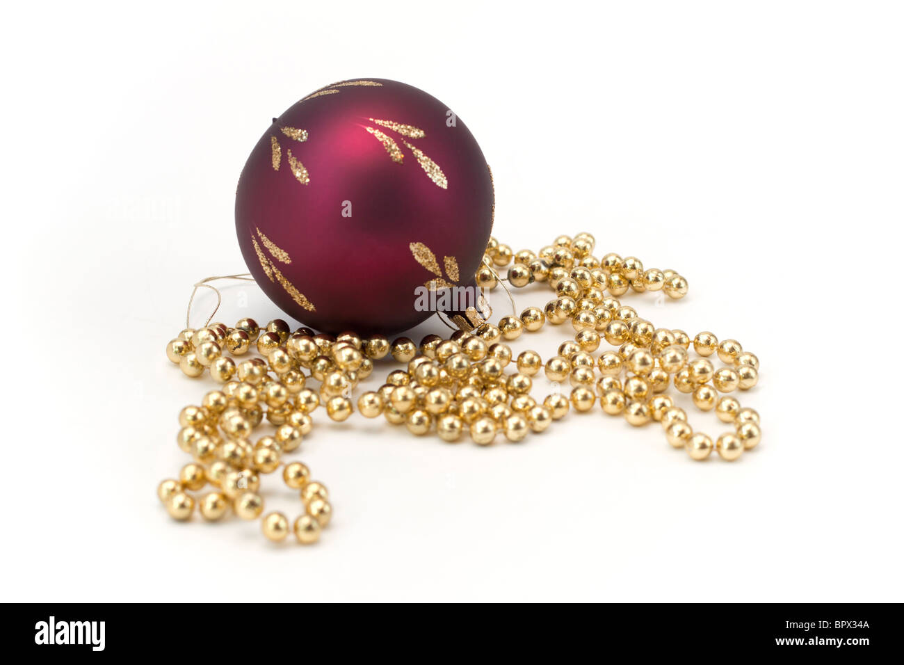 Christmas decorations, a red glass ball and a string of gold beads. Stock Photo