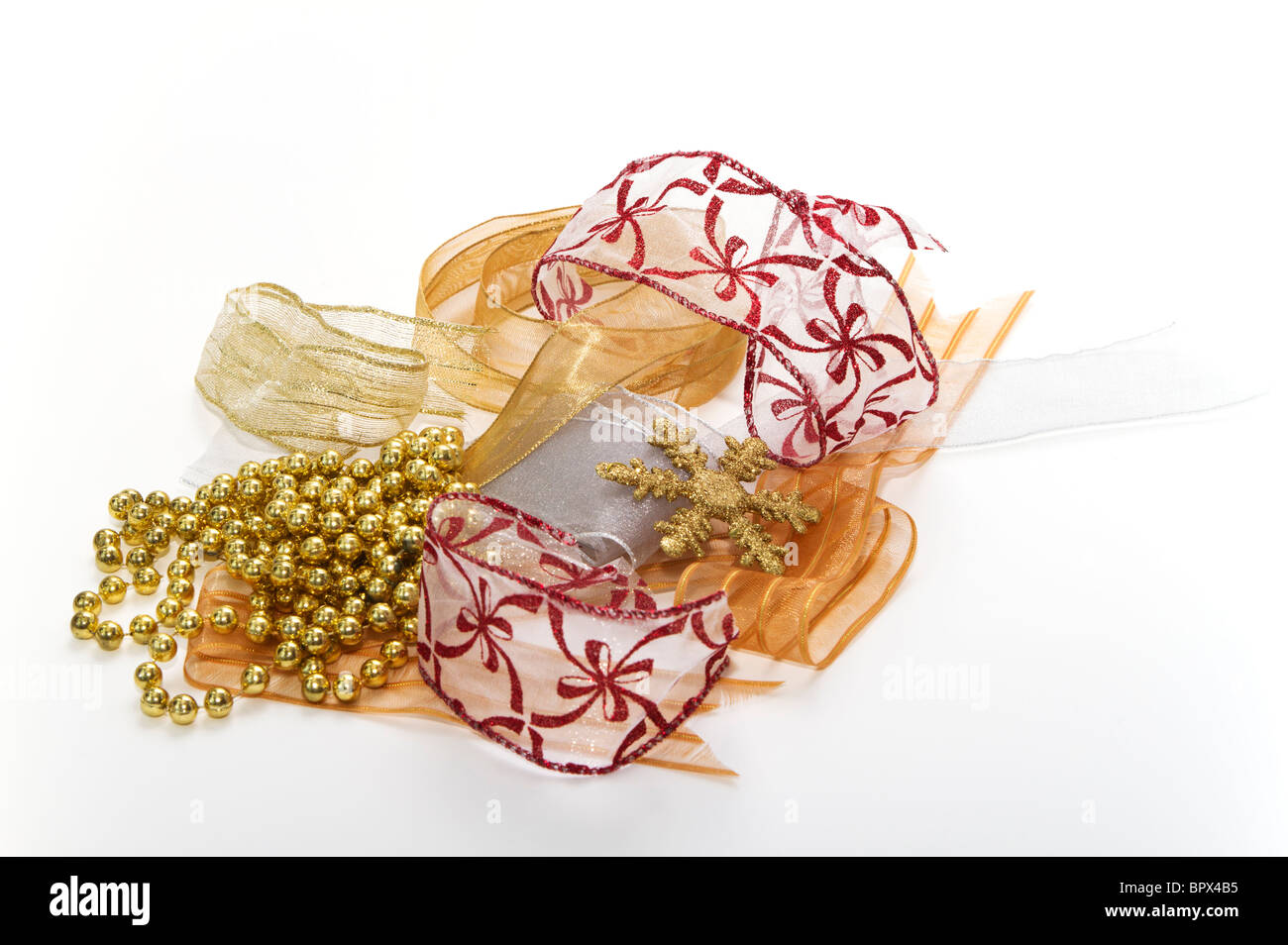 Fancy ribbons for Christmas wrapping with decorations in red, gold, and silver. - Stock Image