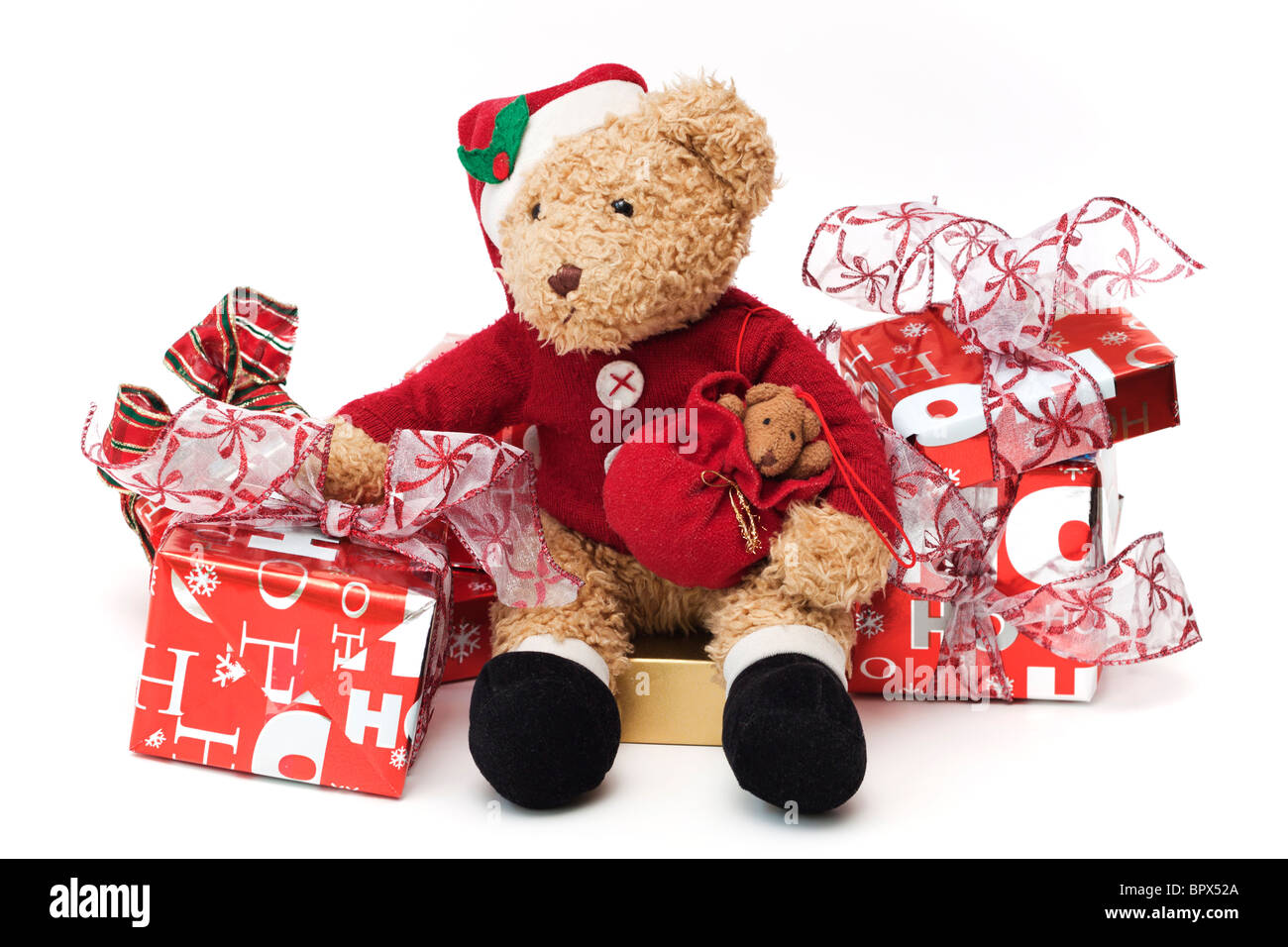 Teddy at Christmas. Well loved child's teddy dressed as Santa Claus sitting among wrapped Christmas presents. - Stock Image