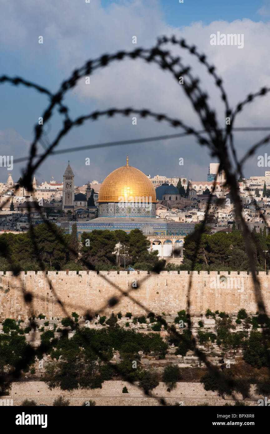 The Old City of Jerusalem, including the Dome of the Rock and various church steeples, seen through coils of razor - Stock Image
