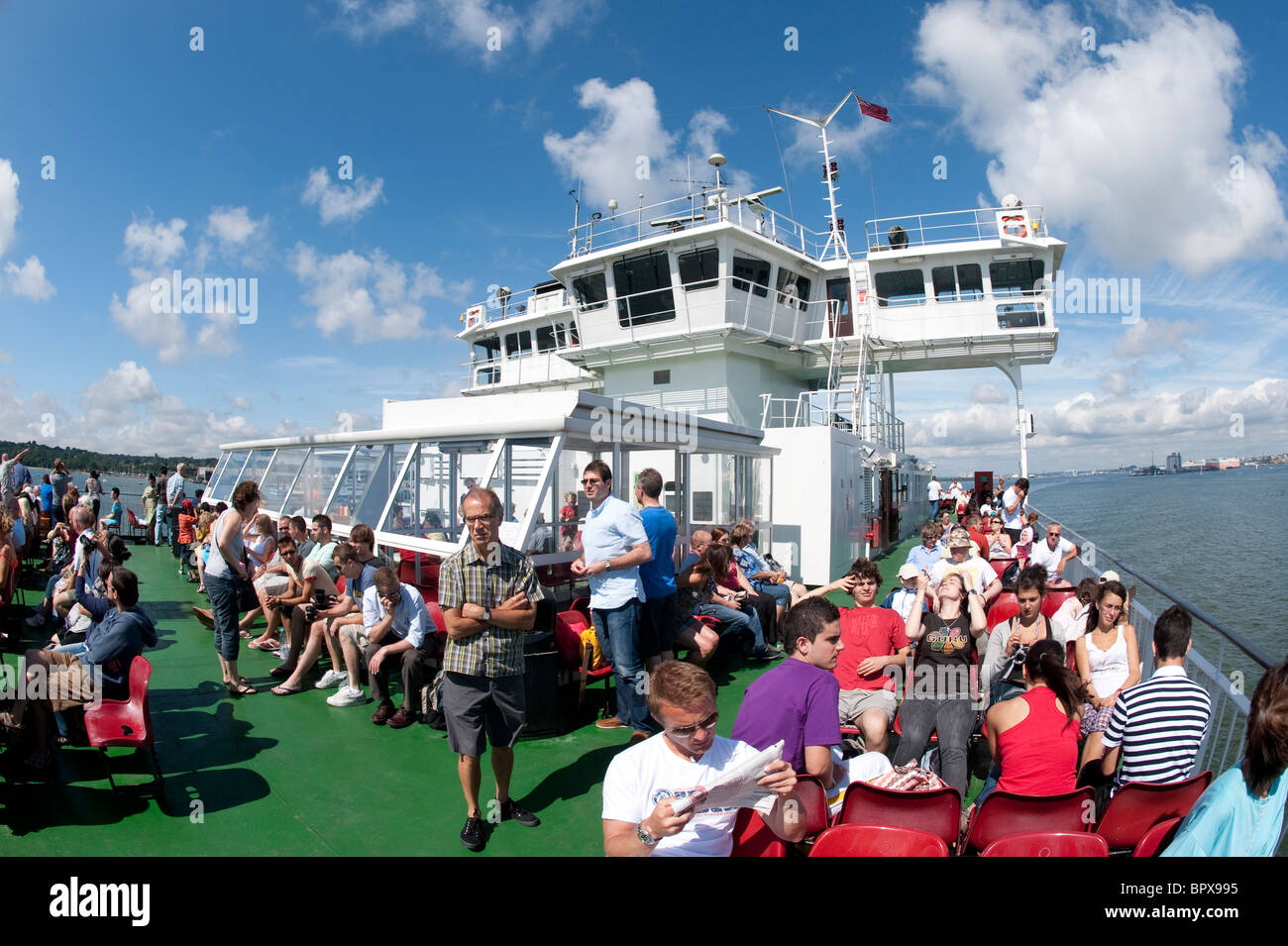 Passengers on the deck of an Isle of Wight ferry sailing across the Solent. - Stock Image