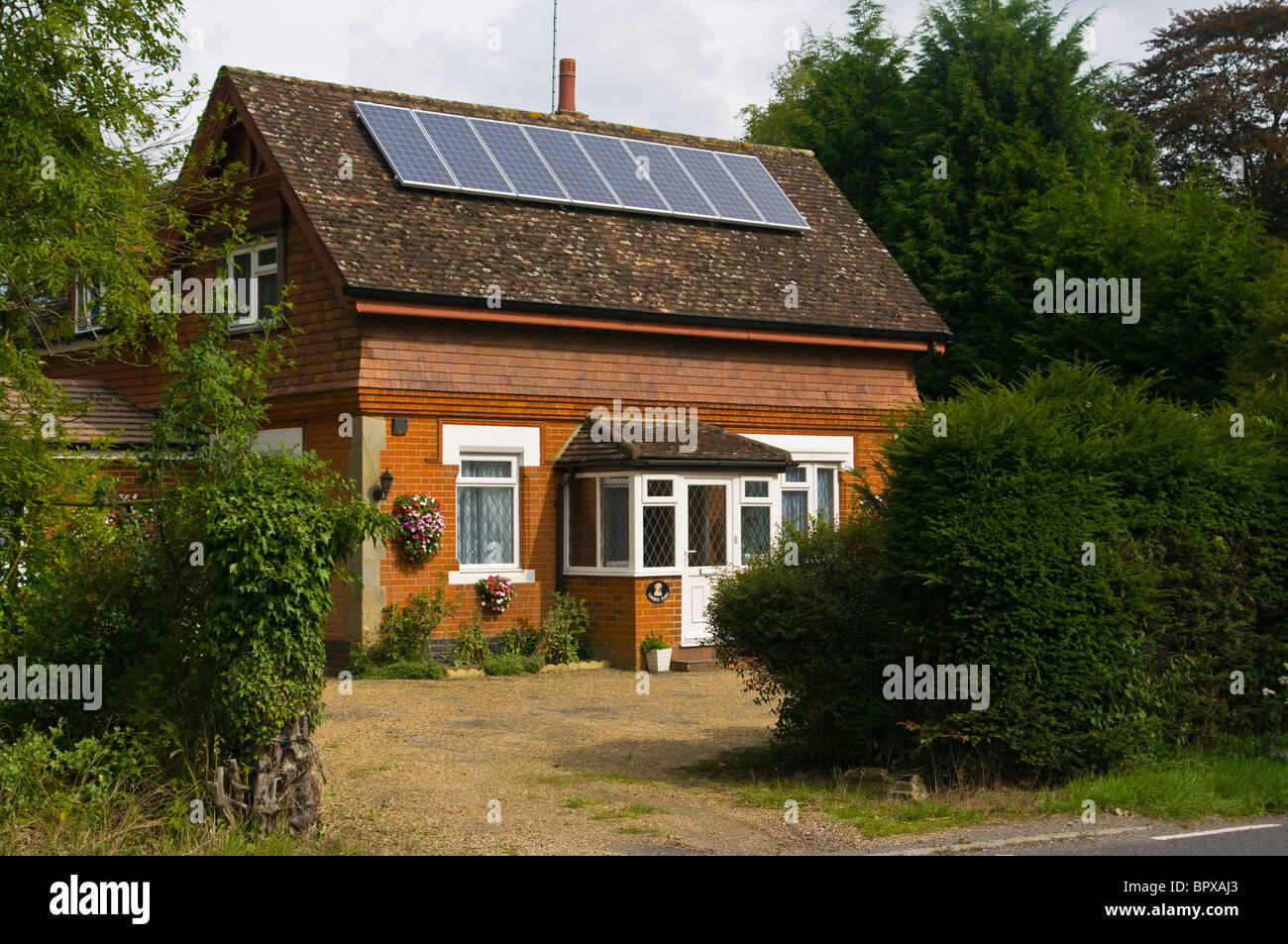 Cottage With Solar Panels On The Roof - Stock Image