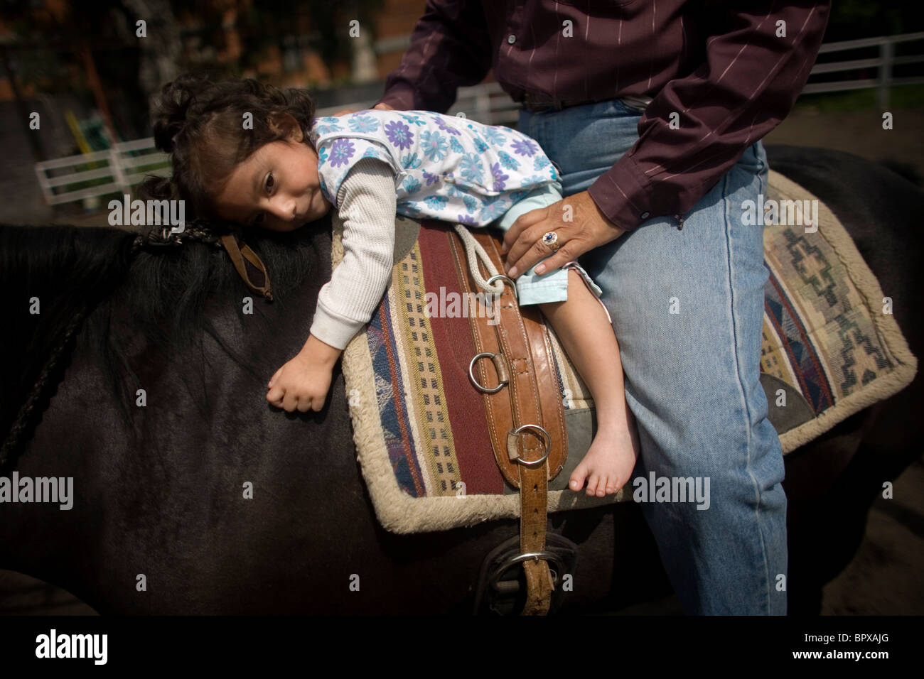 A girl who suffers infantile cerebral paralysis and congenital malformation hugs a horse at a horse therapy session, - Stock Image