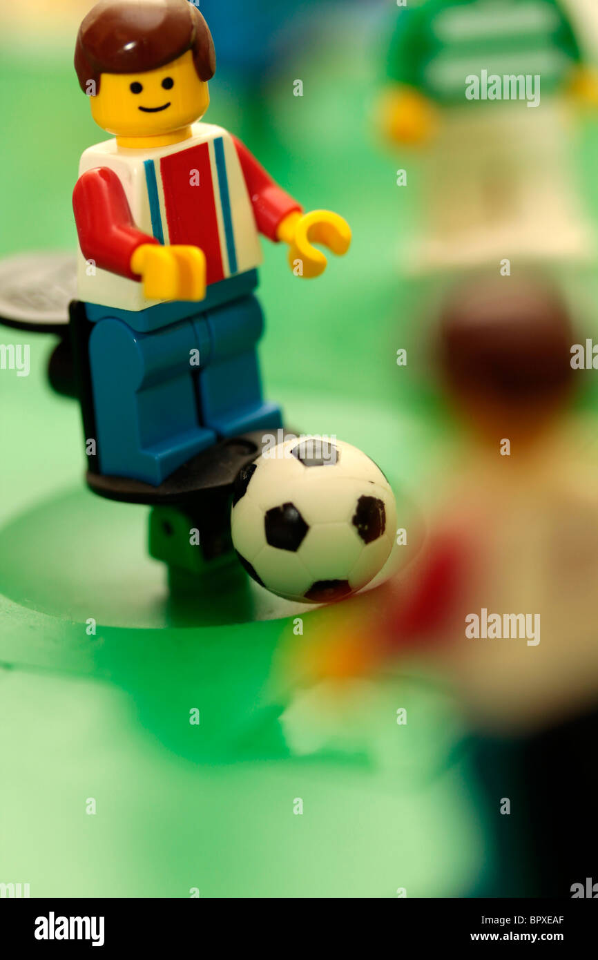 Lego footballer looking to pass the ball to a team mate. - Stock Image