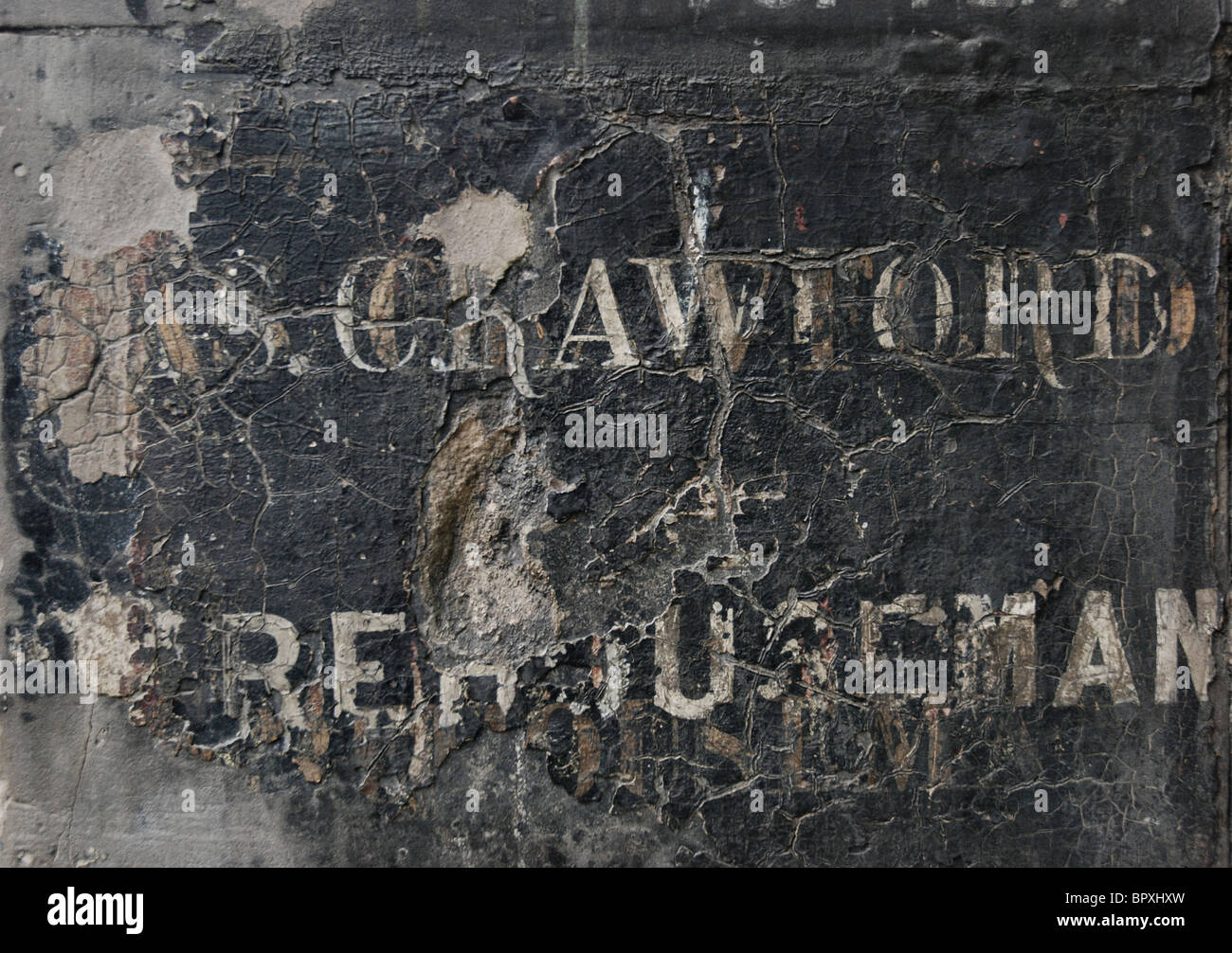 The weathered remains of a painted sign on a wall in Edinburgh's Old Town. Stock Photo