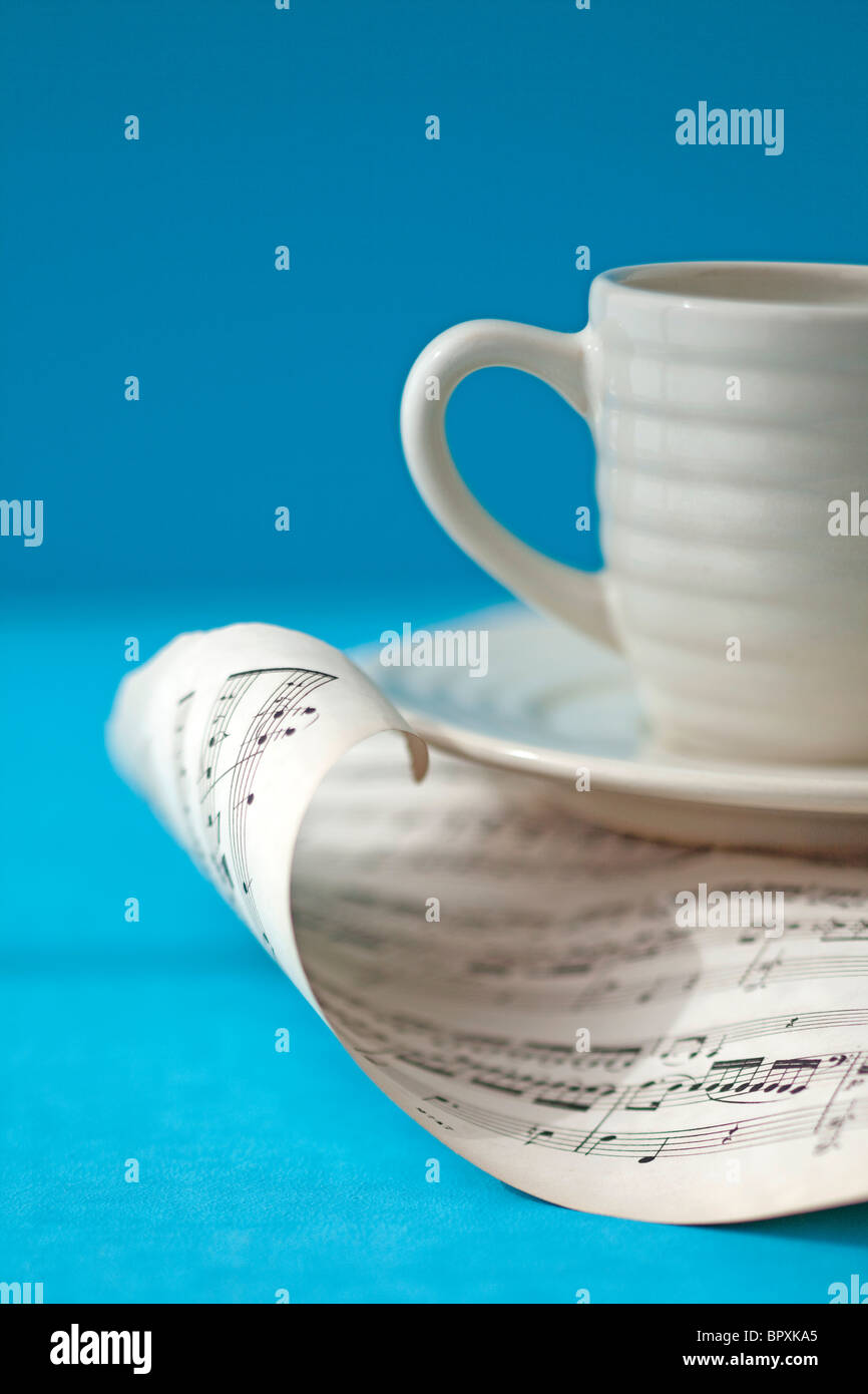 white coffee cup sits on top of curling page of music - Stock Image